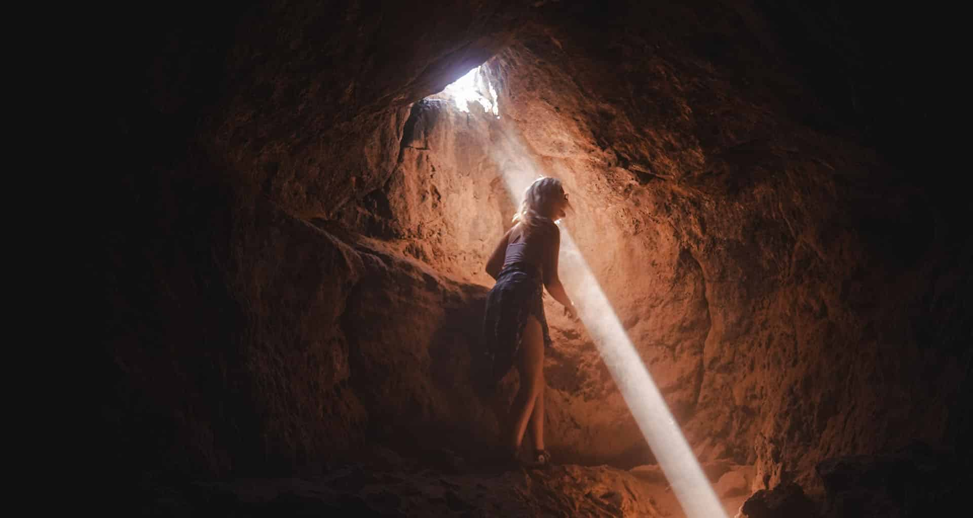 A woman in a cave peers up as light shine from the crack of the cave above.