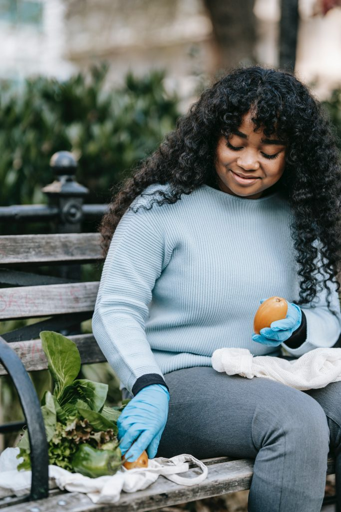 woman in light blue sweater holding fruit and collecting greens while sitting on bench and smiling