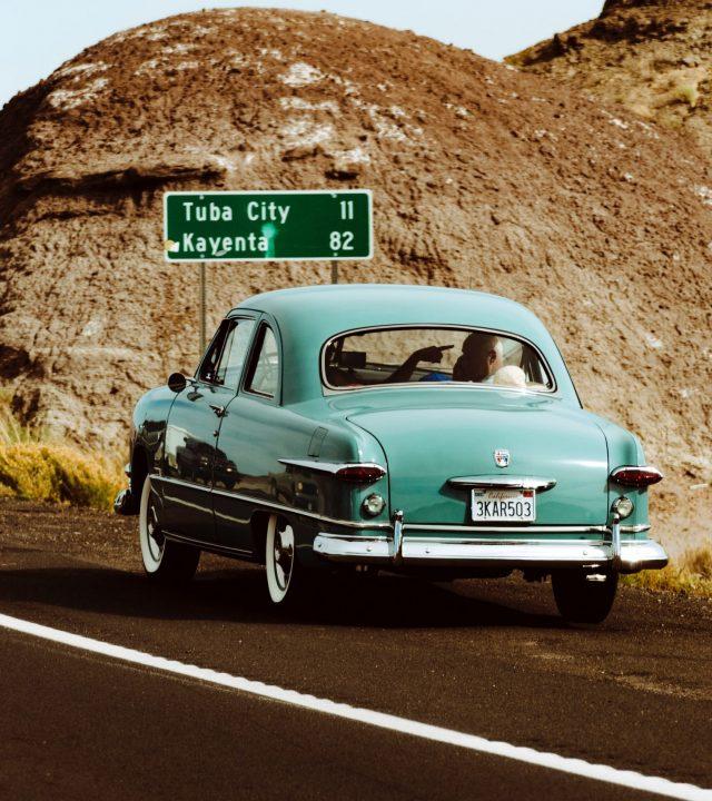 vintage light blue car driving on desert highway