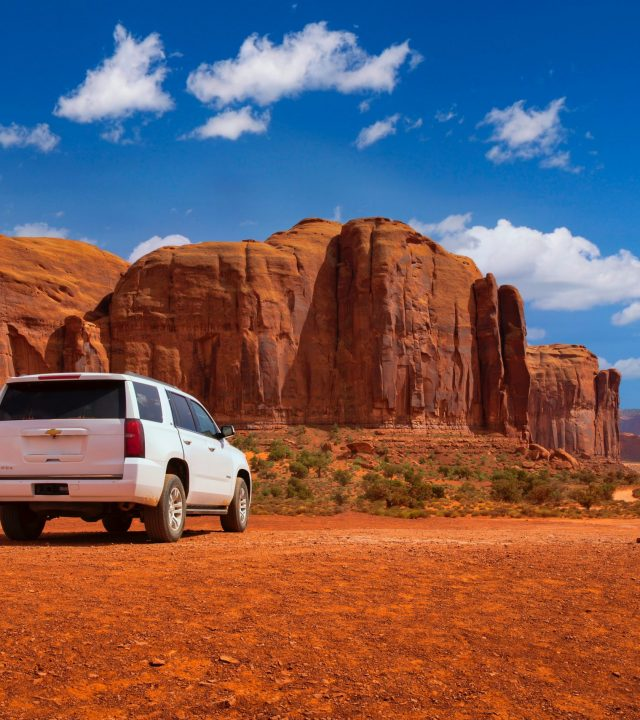 White jeep parked on the Arizona sand with curved mountain beyond the jeep. Blue sky with white clouds.
